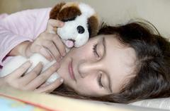 little sweet girl sleeping in a bed hugging with her toy - stock photo