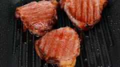Fresh grilled bloody beef steaks on black grill plate Stock Footage