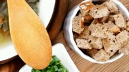 Stock Video Footage of hot fresh diet vegetable soup with rye bread crackers over wood table