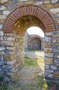 old arched stone passage in the ancient town citadela ruins - stock photo