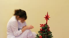 Baby and mother spending time together near the fir tree Stock Footage