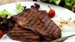 Meat food : two grilled steak on green lettuce salad with red pepper Stock Footage
