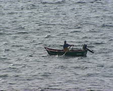 Fisherman rows boat at sea - full screen Stock Footage