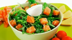 Green salad with salmon and tomatoes on plate Stock Footage