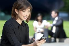 beautiful young asian woman texting and drinking coffee - stock photo