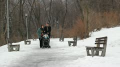 Young happy parents with a baby cart walking on a lonely winter road Stock Footage
