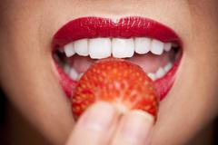 woman holding a strawberry to her lips - stock photo