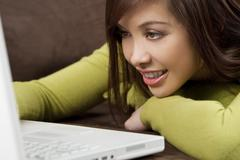 beautiful woman laying down on laptop - stock photo