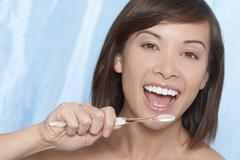 beautiful woman girl brushing her teeth - stock photo