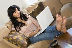 young latin woman girl on sofa relaxing laptop - stock photo
