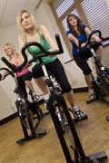 young women exercising spinning class - stock photo