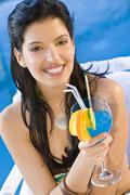 latina woman girl sat by pool drinking cocktail - stock photo