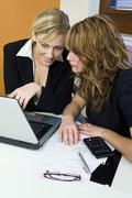 Two women female colleagues office teamwork Stock Photos