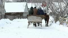 Cart sleigh pulled by horses, full of people passing on a snowed village road Stock Footage