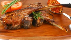 Meat over wood: grilled ribs on plate with tomatoes and spices Stock Footage