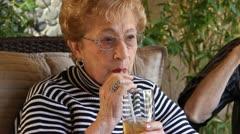 Elderly Woman enjoys cold drink Stock Footage