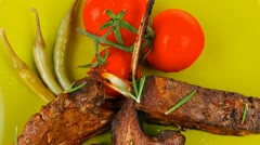Served savory plate: meat ribs with chives and red hot peppers on green Stock Footage