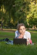 young woman lies on a meadow - stock photo