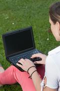 Woman sits on a meadow with a netbook Stock Photos