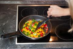 woman stirs up vegetables - stock photo