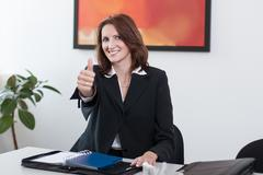 young businesswoman shows thumb up - stock photo