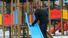 Father cleaning and preparing the blue slide for his child to play Stock Footage