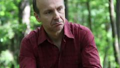 Sad, pensive man sitting and thinking in the forest (2) Stock Footage