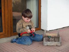 Boy repairing his toy-car Stock Photos
