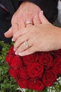 Stock Photo of Wedding red rose bouquet and rings