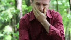 Sad, pensive man sitting and thinking in the forest (7) Stock Footage