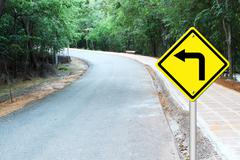 turn left warning sign on curve road - stock photo