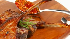 Meat on wooden plate : roast ribs on wood with tomatoes chives and dry spices Stock Footage