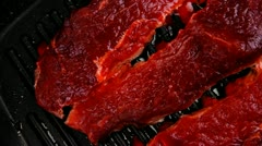 Raw bloody beef fillet steaks on black teflon grill plate  hidef slow motion Stock Footage