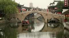 Qibao Ancient Town traditional stone arch bridge and wooden boat Stock Footage