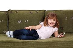 Iloinen pikkutyttö makaa sängyllä ja kuuntelee musiikkia puhelimeen Kuvituskuvat