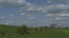Dog walker on dike in Dutch river landscape - wide  shot Stock Footage