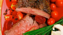 Roasted meat served on red dish with vegetables Stock Footage