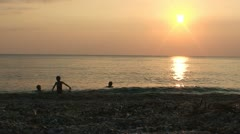 Silhouettes of  3 children playing  at shallow sea, in the sunset. WS, Lockdown Stock Footage