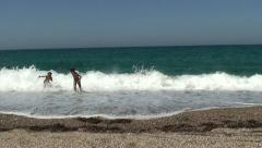 Children playing with waves and running at the beach. WS, Handheld Stock Footage