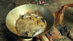 Frying Fish over Open Flame Stock Footage