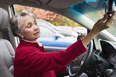 Mixed race woman adjusting car mirror Stock Photos