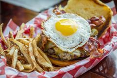 Basket of french fries with cheeseburger and egg Stock Photos