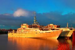 Marine sunset on the dutch shipyard. new unpainted vessels in sunlight. nethe Stock Photos