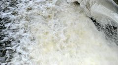 Closeup strong water stream flow spray retro dam ice snow winter Stock Footage