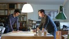Two architects examining a plan in an office (dolly) - stock footage