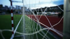 People walk behind the Goal Post at the football stadium. WS, Handheld Stock Footage