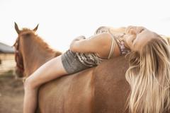 Caucasian girl laying on horse Stock Photos