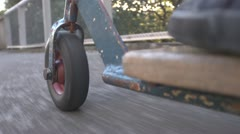 Retro push scooter, POV downhill sidewalk Stock Footage