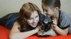 Girl and a woman stroking a cat and a fun talking Stock Footage