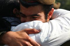 Golani recruit hug with a relative after receiving brown beret - stock photo